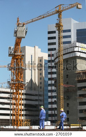 Two asian construction workers on a pile of rebars in front of a construction area in Doha, Qatar, with cranes and high-rise buildings beyond. - stock photo