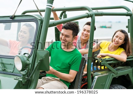 Two Asian couples traveling by off-road car - stock photo