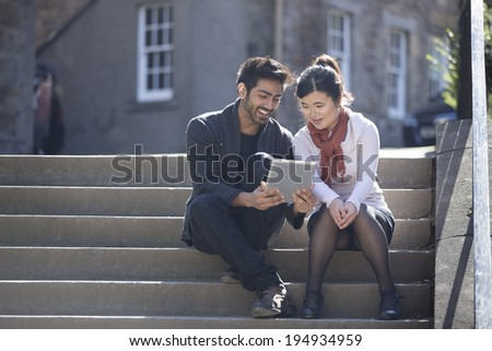 Two Asian friends sitting outdoors using digital Tablet. Young urban couple 'hanging out' and using tech in the city. - stock photo