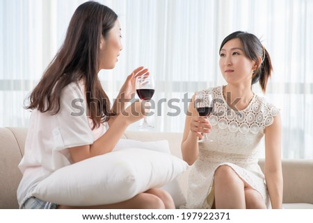 Two Asian friends talking and drinking wine at home
