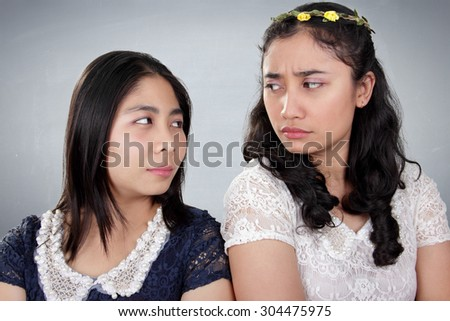 Two Asian girls in bad situation, looking against each other with hateful stares, over grey background - stock photo