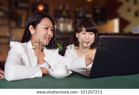 Two Asian girls using a laptop in the coffee shop. - stock photo