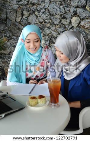 Two asian Muslim young woman was chatting with a book