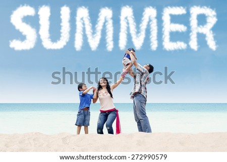Two asian parents playing with their children on the tropical shore under a summer's cloud - stock photo