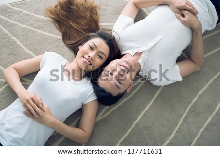 Two Asian siblings lying head to head - stock photo