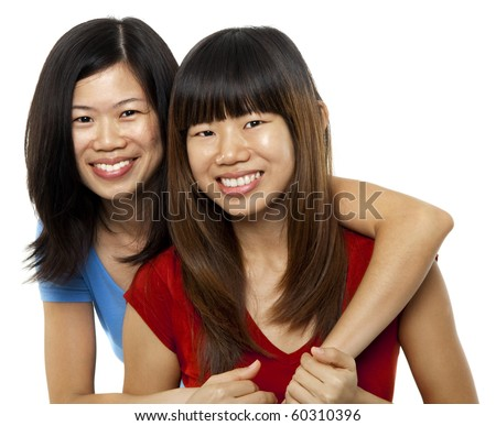 Two Asian sisters isolated on white background - stock photo