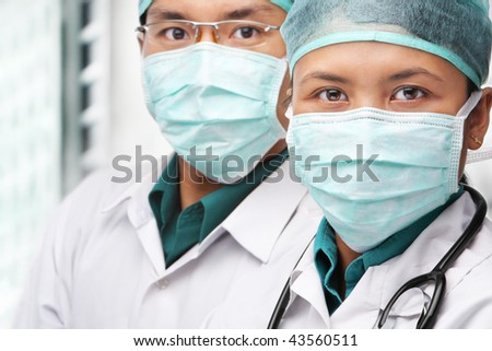 Two Asian surgeon posing to camera with protective gear