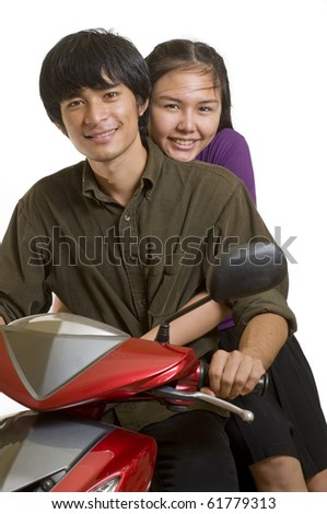 Two Asian teenagers on a motorbike - stock photo
