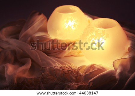 Two asian-themed lamps nestled in a scarf. - stock photo