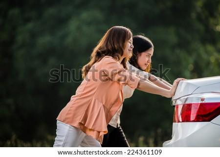 Two Asian women Are broken down car - stock photo