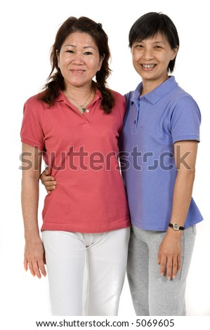 Two Asian women standing together in studio on white background - stock photo
