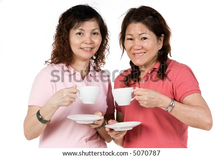 Two Asian women standing together with cups and saucers in studio on white background