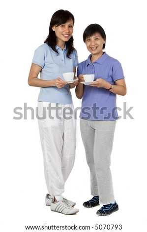 Two Asian women standing together with cups and saucers in studio on white background - stock photo