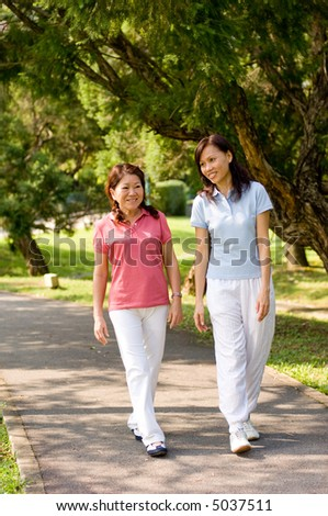 Two Asian women walking in the park talking to each other - stock photo