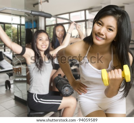 Two Asian young women with exercise equipment at the gym - stock photo