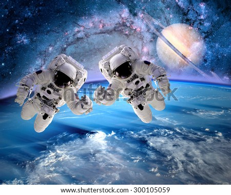 Two astronauts spaceman outer space saturn planet earth universe. Elements of this image furnished by NASA. - stock photo