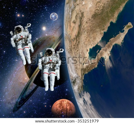 Two astronauts spaceman solar system saturn  planet moon sci fi space. Elements of this image furnished by NASA.