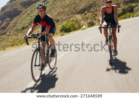 Two athletes going down the hill on racing bicycles. Man and woman cyclist riding down the country road. Triathlon training. - stock photo