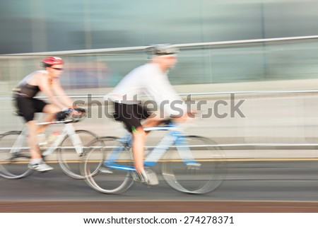 Two Athletes riding bicycle in the city, blurred motion. - stock photo