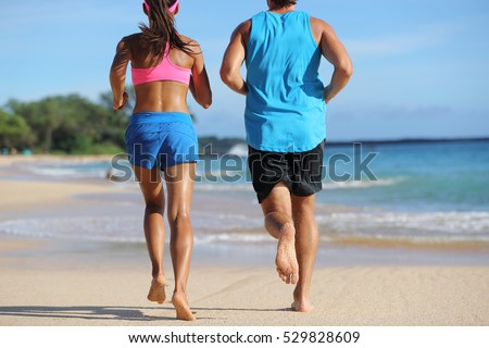 Two athletes runners couple running together on beach. People from behind jogging away barefoot on sand on tropical travel destination. Lower body, legs, feet.