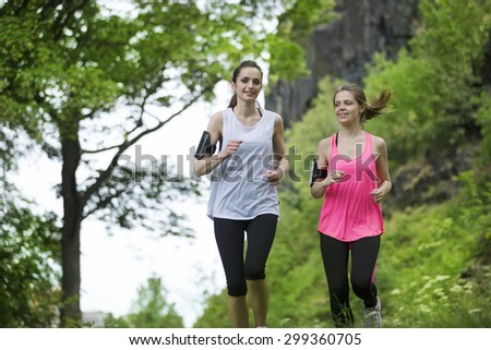 Two athletic women running outdoors. Action and healthy lifestyle concept.