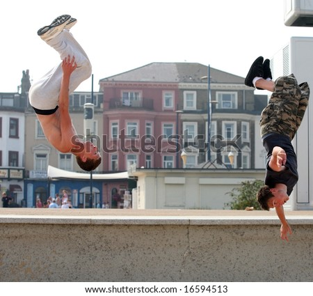 "Two athletic young Britons engage in their passion for ""parkour"" or ""free running"" on the seafront at Great Yarmouth - stock photo"