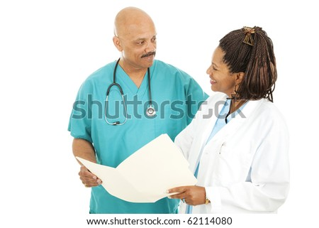 Two attractive, African American doctors discussing a patient's medical chart.  Isolated on white.