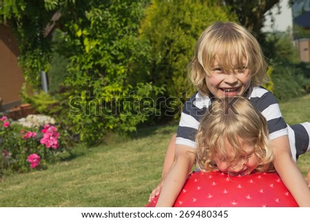Two attractive blond boys are playing with red gymnastic ball outdoors - stock photo