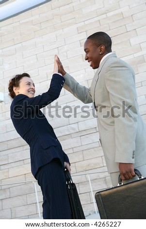 Two attractive business people celebrating a success - stock photo