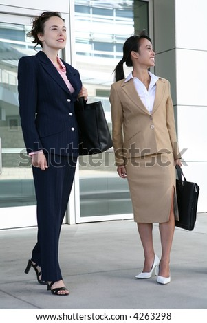 Two attractive business woman leaving their company - stock photo