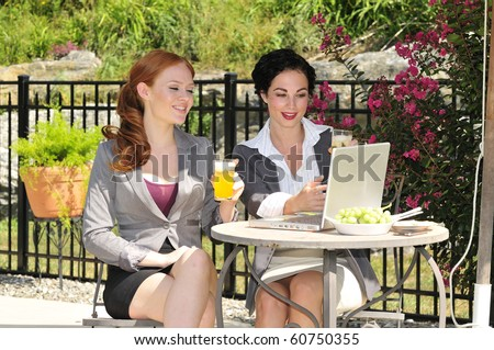 two attractive business women having a casual lunch meeting - stock photo