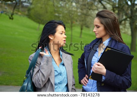 two attractive businesswoman in park, both wear shirt and suit, elegant look, outdoor shoot - stock photo
