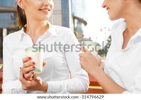 Two attractive businesswoman talking during coffeebreak outdoors - stock photo