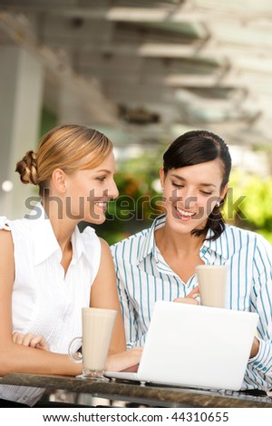 Two attractive businesswomen chatting over coffee - stock photo
