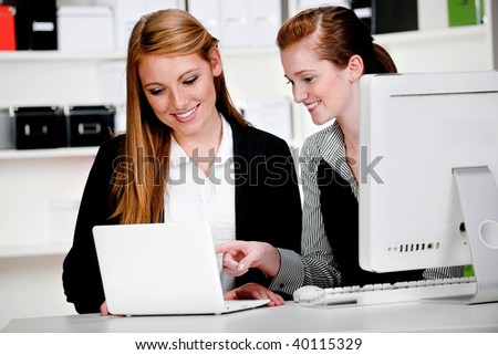 Two attractive businesswomen discussing work in front of a computer and a laptop in the office