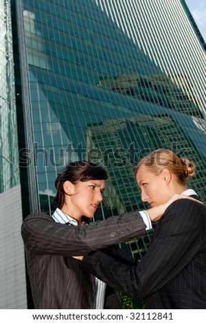Two attractive businesswomen fighting against city backdrop - stock photo