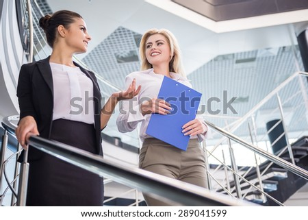 Two attractive bussiness women moving down the stairs and talking. - stock photo