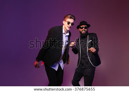 Two attractive cheerful young men in sunglasses dancing over purple background