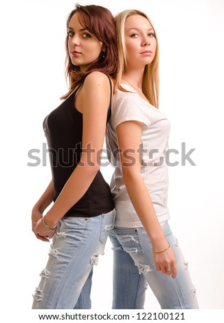 Two attractive curvy young woman in casual jeans and summer tops standing back to back sideways to the camera, studio portrait isolated on white - stock photo