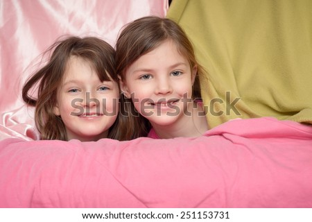 Two attractive cute little girl friends smiling at the camera over the top of a pink draped sofa with just their heads visible - stock photo