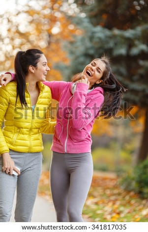 Two attractive female at the park.They looking something on phone.Friend hug. - stock photo