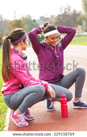 Two attractive female at the race track.Jogging pause. - stock photo