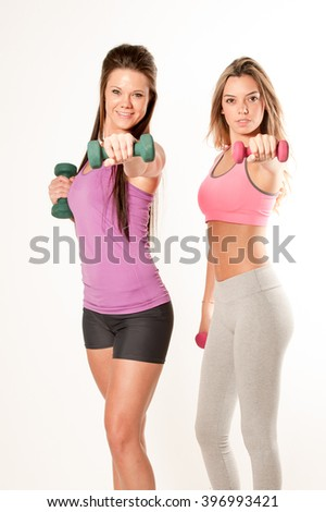 Two Attractive female fitness models isolated on a white background in sports wear with dumbells