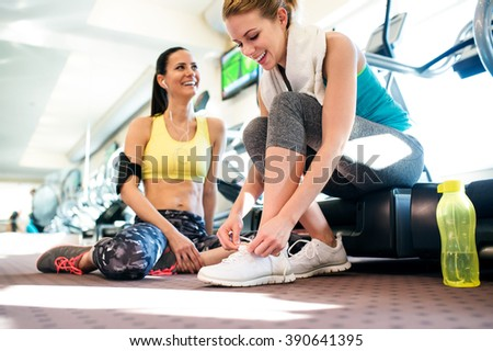 Two attractive fit women in gym preparing for workout