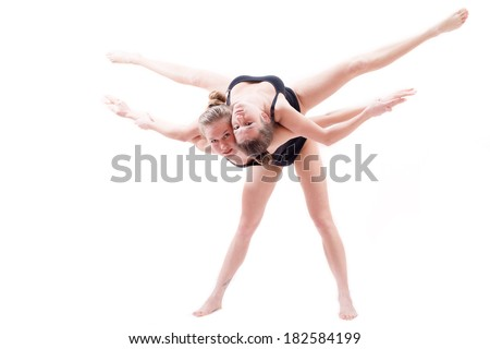 two attractive flexible athletic women pretty girl friends raised one another on the back doing split in the air & looking at camera - stock photo