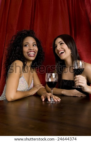 Two attractive friends drinking wine - stock photo