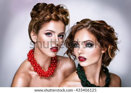 Two attractive girl friends - blond and brunette on white background with necklaces and strong style - stock photo