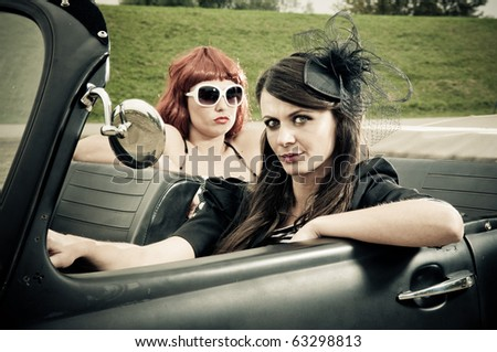 Two attractive girls driving around in vintage car - stock photo