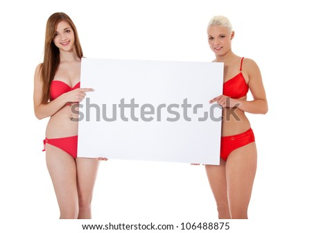 Two attractive girls in bikini holding blank white sign. All on white background. - stock photo