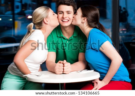 Two attractive girls kissing handsome young boy in a restaurant. - stock photo